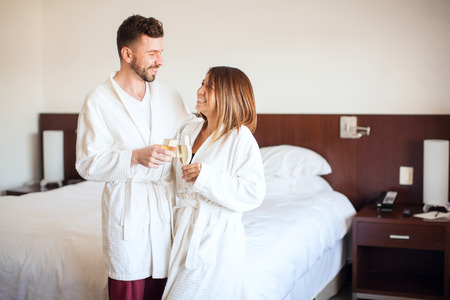 Happy couple wearing robes in a hotel room and making a toast with champagne during their honeymoon Stock Photo