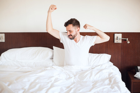 Handsome young man waking up and stretching on his bed right after waking up in the morning