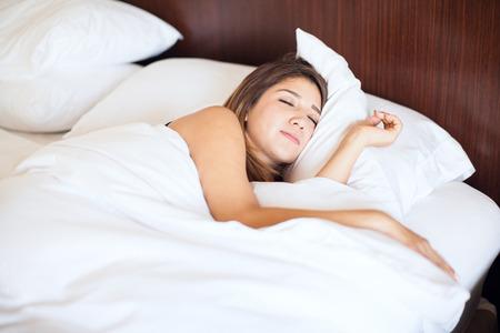 mujer sola: Bastante joven morena conseguir un poco de sueño en una cama muy cómoda en un hotel