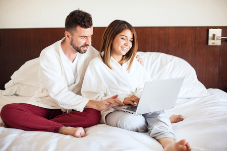 pj's: Portrait of a young couple using a laptop computer while sitting in a bed at a hotel