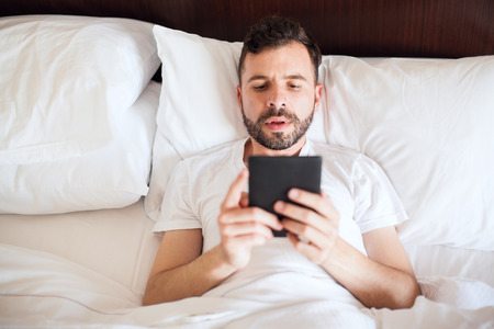 Good looking young man using an e-reader to read a book in bed early in the morning