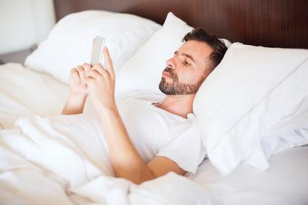 pj's: Attractive young man with a beard using a smartphone and texting while lying on his bed Stock Photo