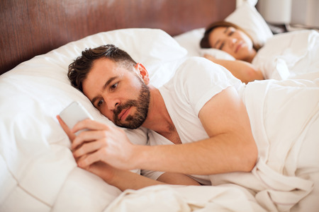 Portrait of a handsome young man with a beard checking his smartphone and texting his lover while his partner sleeps
