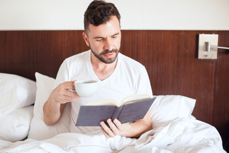 Attractive man with a beard drinking coffee and reading a good book in his bed in the morning