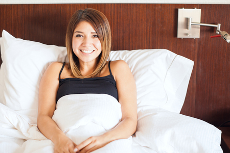 hispanic woman: Portrait of a gorgeous Hispanic woman waking up with a smile, feeling optimistic and happy Stock Photo