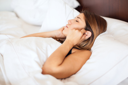 pj's: Profile view of a cute young woman putting some earplugs on before going to sleep in a hotel bed Stock Photo