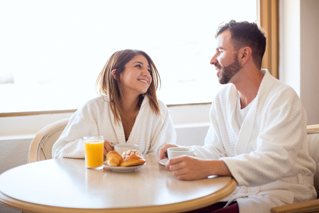 Good looking young couple wearing robes and eating breakfast in their hotel room
