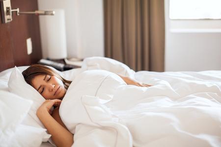 mujer sola: Joven y bella morena de conseguir un poco de descanso y dormir hasta tarde por la mañana en una cama de hotel