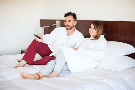 tv show: Young couple relaxing at home and watching a TV show while lying on a bed