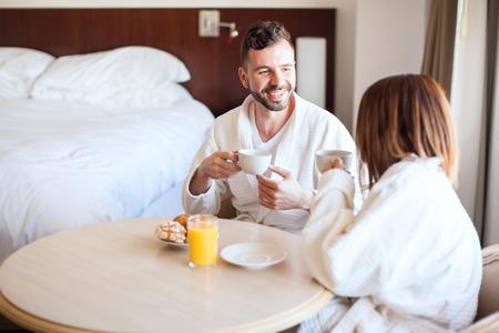 luna de miel: pareja de hispanos joven que goza de una taza de café y el desayuno en su habitación de hotel durante su luna de miel