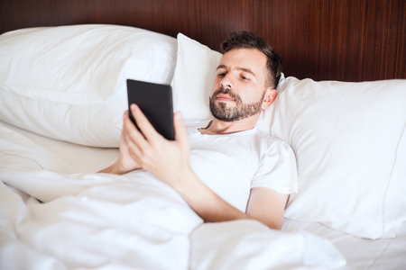 favorite book: Handsome man with a beard using an e-reader to read his favorite book in bed Stock Photo