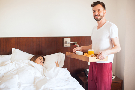 Portrait of a handsome young man surprising his girlfriend with breakfast in bed at home