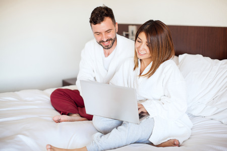 pj's: Pretty young couple wearing robes and sitting on a bed using a laptop computer during their vacation