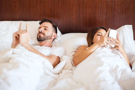 Young couple ignoring each other in bed while using their own smartphones to read their social media feeds