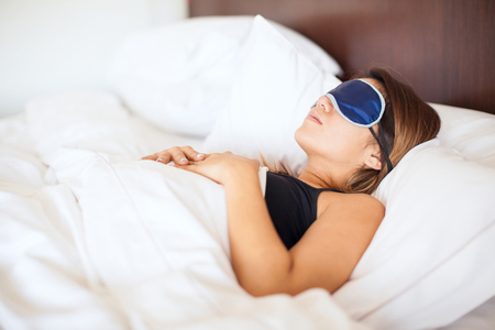 sleep mask: Profile view of a young woman wearing a sleep mask in a comfortable bed at a hotel Stock Photo