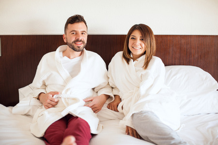 pj's: Pretty young couple wearing robes and relaxing in a hotel bed during a vacation trip and smiling