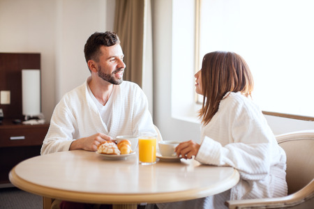 Cute young Hispanic couple wearing robes and eating breakfast in a hotel room during their honeymoon Stock Photo
