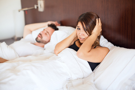 cant: Stressed young woman covering her ears while her husband snores at night and she cant sleep Stock Photo