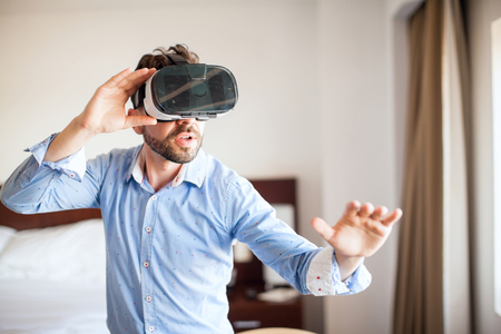 adult entertainment: Young man with a beard dressed casually using virtual reality glasses and looking amazed