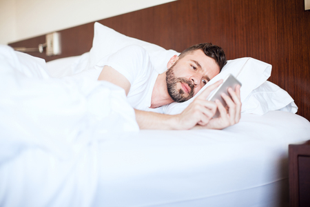 pj's: Good looking young man using his smartphone and texting while lying on his bed