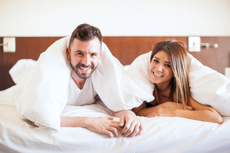 pj's: Cute young Hispanic couple relaxing in a hotel bed and snuggling together during their honeymoon