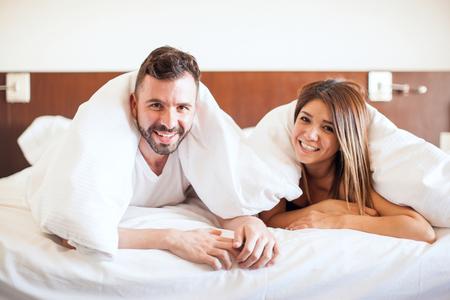 Nette junge hispanische Paare in einem Hotelbett entspannen und zusammen während ihrer Flitterwochen Kuscheln Standard-Bild - 63170217