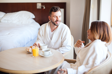 pj's: Portrait of a young man with a beard having breakfast with his partner while enjoying their vacations in a hotel