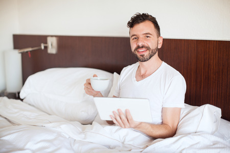 pj's: Portrait of a good looking Hispanic young man reading the morning news in a tablet computer while drinking coffee in bed