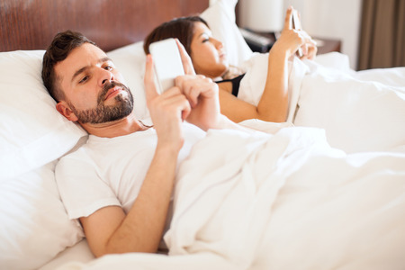Portrait of a young man with a beard and his wife both using their smartphones while lying together in bed