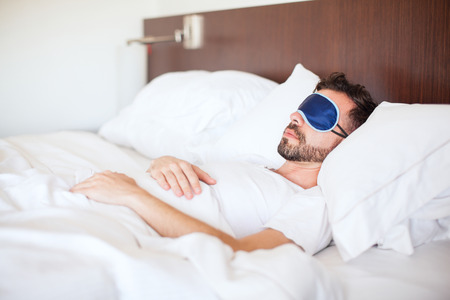 sleep mask: Portrait of a young man with a beard using a sleep mask to get some rest in a hotel