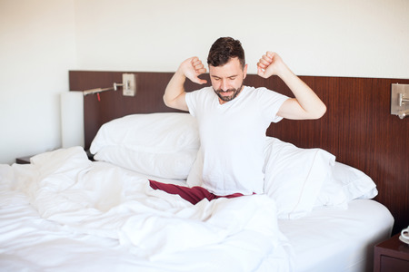 pj's: Young man with a beard stretching and yawning right after waking up in the morning in a hotel bed