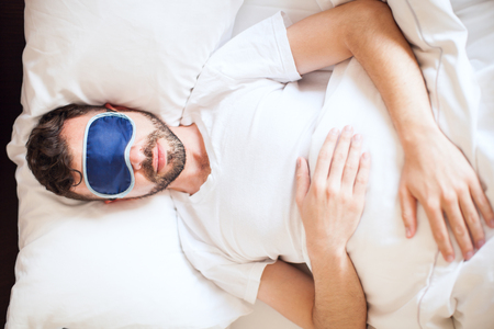 Top view of a young man wearing a sleep mask while getting some rest in his bedroom Stock Photo
