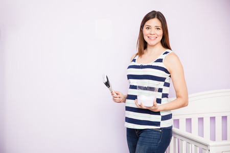woman pregnant: Cute young pregnant woman painting and decorating the babys room and smiling