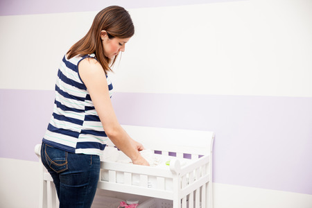 organizing: Attractive young pregnant woman storing diapers and organizing her diaper changing station in a nursery at home Stock Photo
