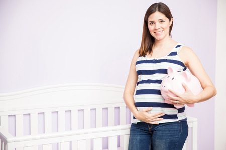 Gorgeous young Hispanic pregnant woman holding a piggy bank while standing next to a baby crib at home