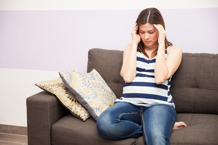 headaches: Good looking young woman suffering from migraine and headaches during her pregnancy