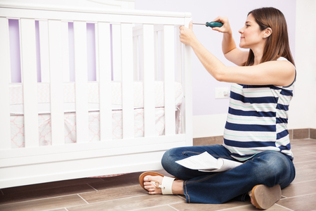 baby crib: Pretty young pregnant woman assembling a baby crib in a nursery before the baby arrives Stock Photo