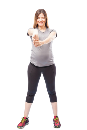 expectant arms: Pretty young pregnant brunette stretching her arms and working out against a white background