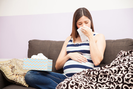 Portrait of a young pregnant woman feeling sick at home and blowing her nose with a tissue