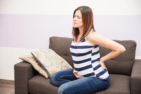 매력적인 젊은 갈색 머리 집에서 휴식하는 동안 그녀의 임신 중에 허리 통증을 느낌 스톡 콘텐츠