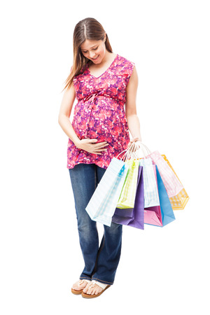 Full length view of a young pregnant woman buying clothes and other items for her unborn baby on a white background