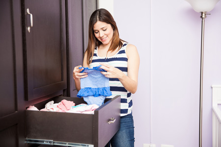 Attractive young pregnant brunette folding and storing baby clothes on a closet in a nursery before the baby's arrival