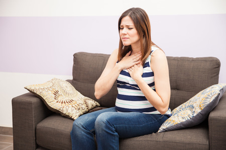 Cute young woman at home suffering from heartburn during her pregnancy Banco de Imagens