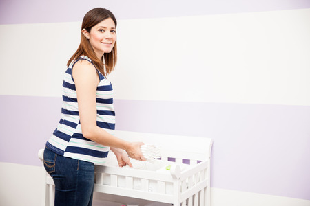 young diapers: Portrait of a beautiful young pregnant woman storing some diapers and other supplies for her changing station in a nursery Stock Photo