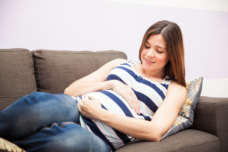 expectant: Beautiful young expectant mom embracing her belly and waiting for her due date