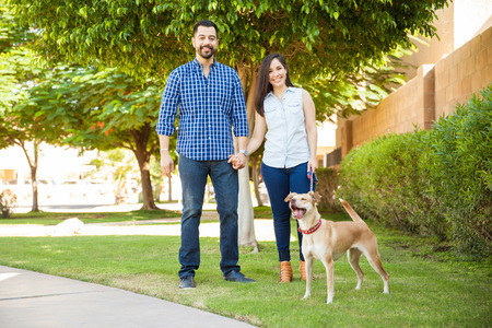 Portrait of a beautiful Hispanic couple going for a walk at a park with their friendly dog and smiling Stock Photo
