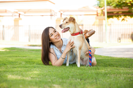 hispanic woman: Attractive young brunette lying on the grass with her dog in a park and having a good time