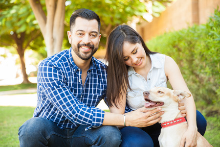 petting: Portrait of a good looking young couple spending time with their dog and petting her at a park Stock Photo