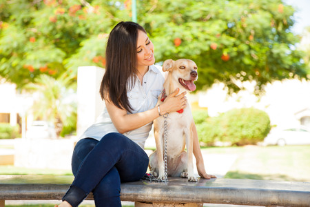 petting: Pretty young brunette relaxing outdoors by sitting in a park bench with her dog and petting her
