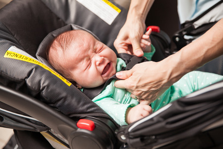 baby carrier: Very upset newborn baby crying after her mom just put her in a baby carrier Stock Photo